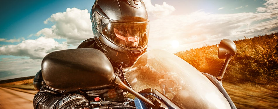 Man riding at the sunset wearing a motorcycle racing helmet