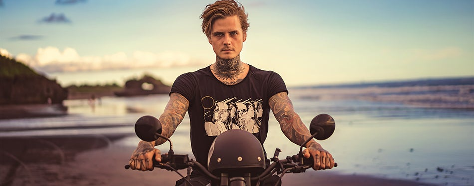 Tatooed man riding his motorcycle on the beach while wearing a motorcycle t shirt