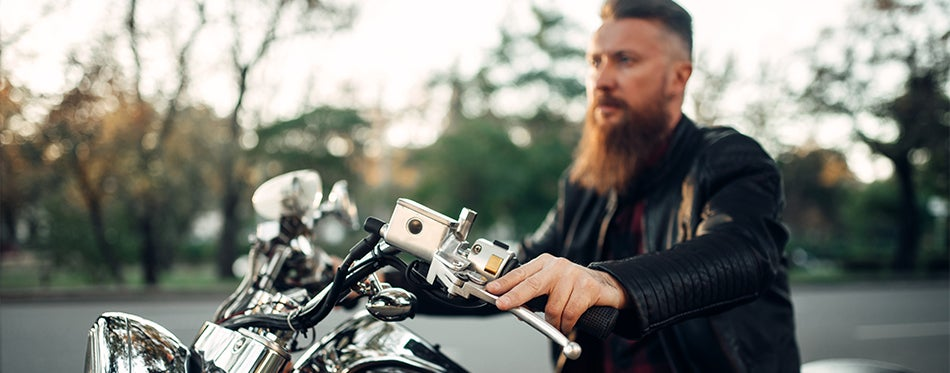 Bearded man riding his motorcycle with thermometer