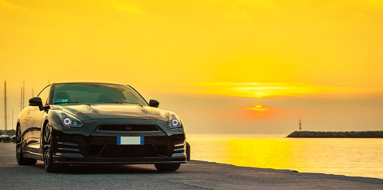 Black Nissan GTR at the beach during a sunset
