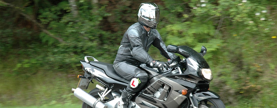 Motorcyclist with a black scorpion helmet on the road