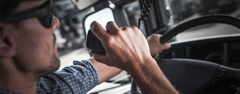 Trucker using handheld radio to communicate