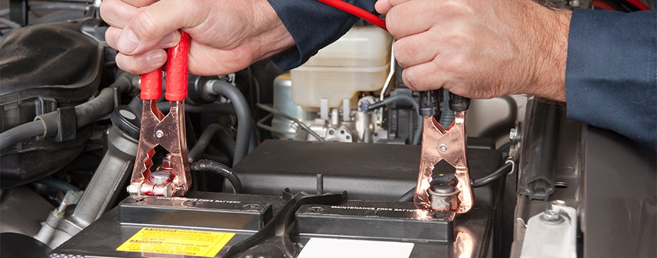 Man jumpstarting car battery in cold weather