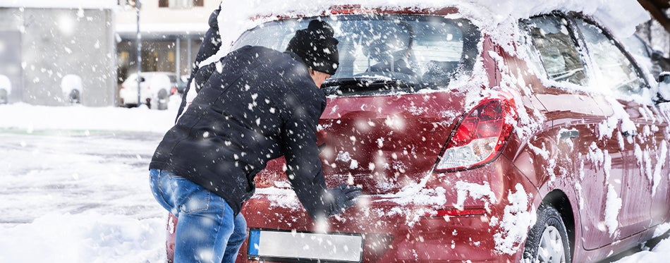 Man pushing a car with bad battery in cold snowy weather