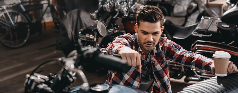Man working on his motorcycle while drinking coffee