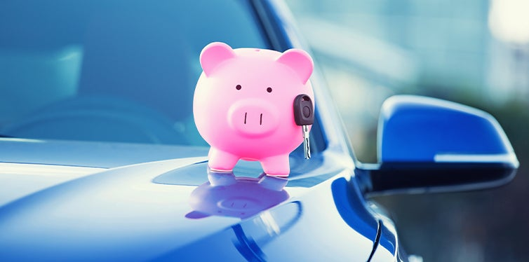 Piggy bank and keys on top of car