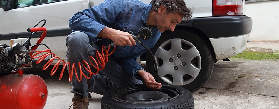 Repairman inflating tire with shop air compressor