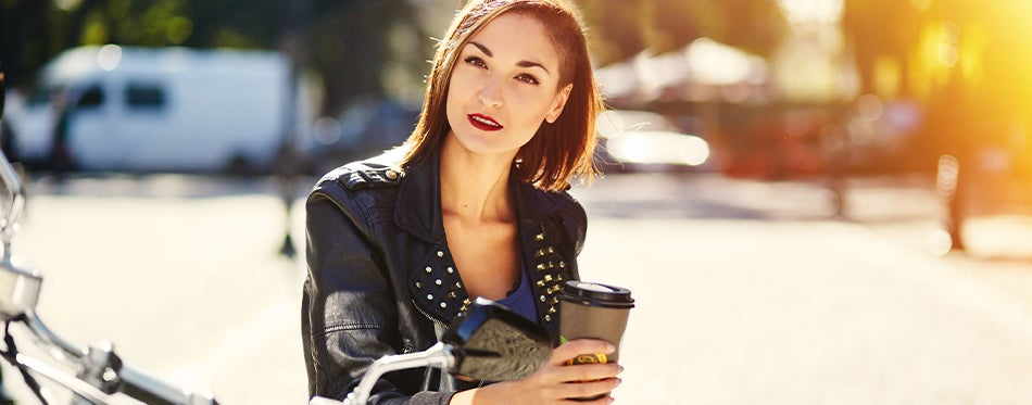 Woman drinking coffee on her motorcycle with motorcycle cup holder