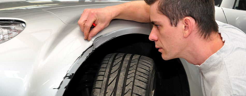 man fixing scratch with car paint chip kit