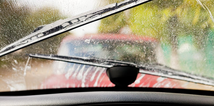 Cleaning car windshield with the windshield wipers