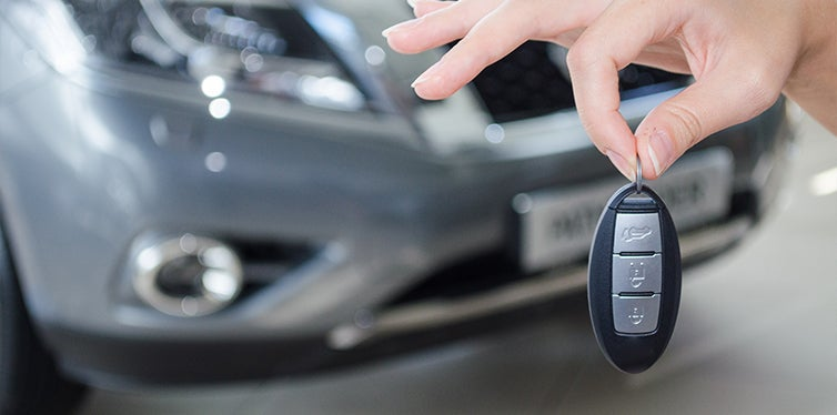 Reprogrammed car key fob in front of car