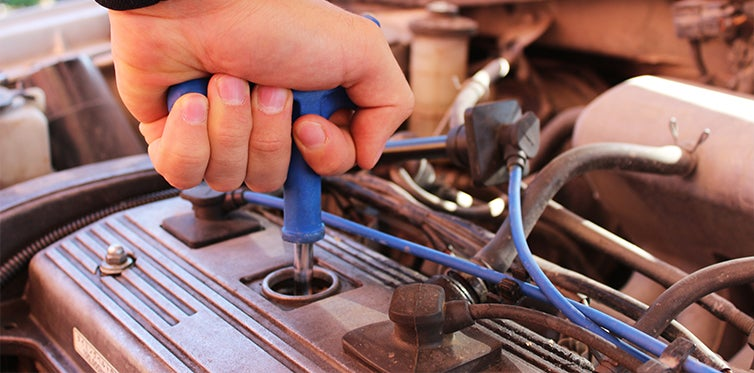 Mechanic removing spark plug from car