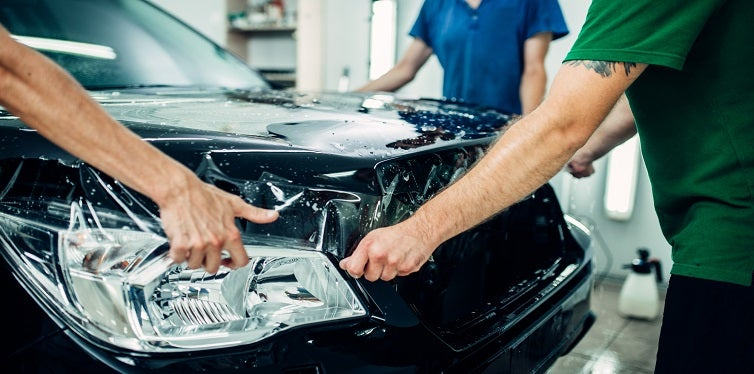 Workers wrap car hood in protective coating