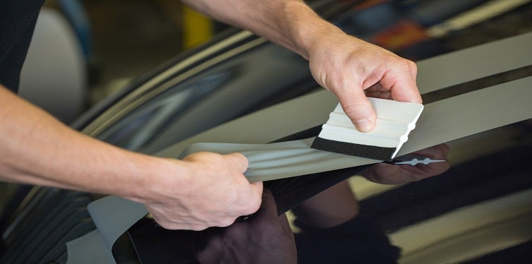 Car wrapping foil with a squeegee to remove air bubbles