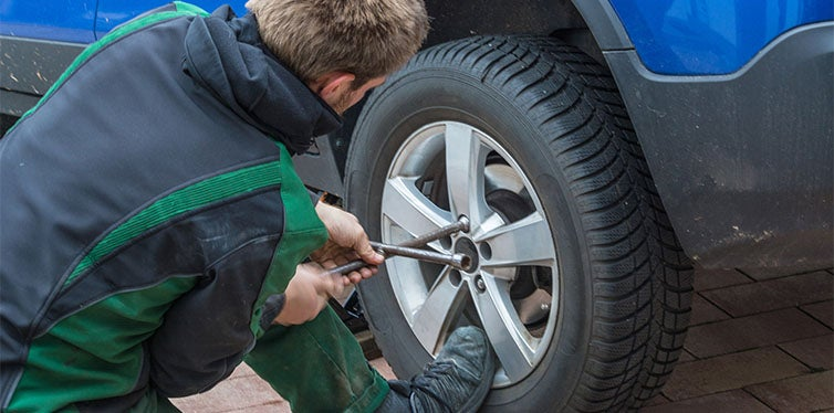 Guy using torque wrench to remove the wheel