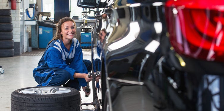 Woman changing the front tire using torque wrench