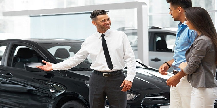 Сar Salesman Invites Customers at Showroom