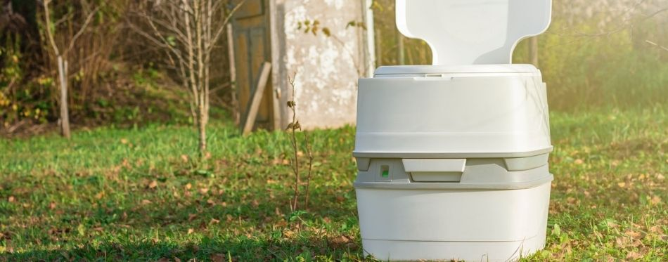 A portable plastic toilet in the woods