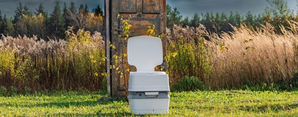 A portable plastic toilet in the foreground