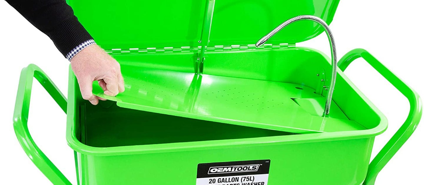 Man hand opening a green parts washer