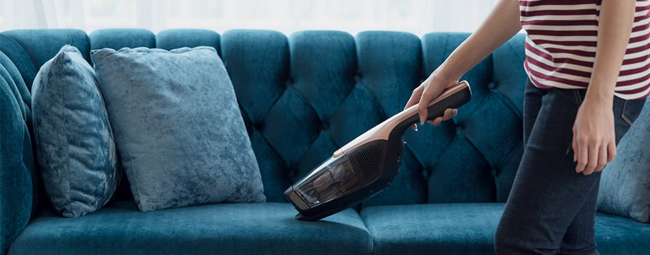 women using portable vacuum cleaner to clean the couch