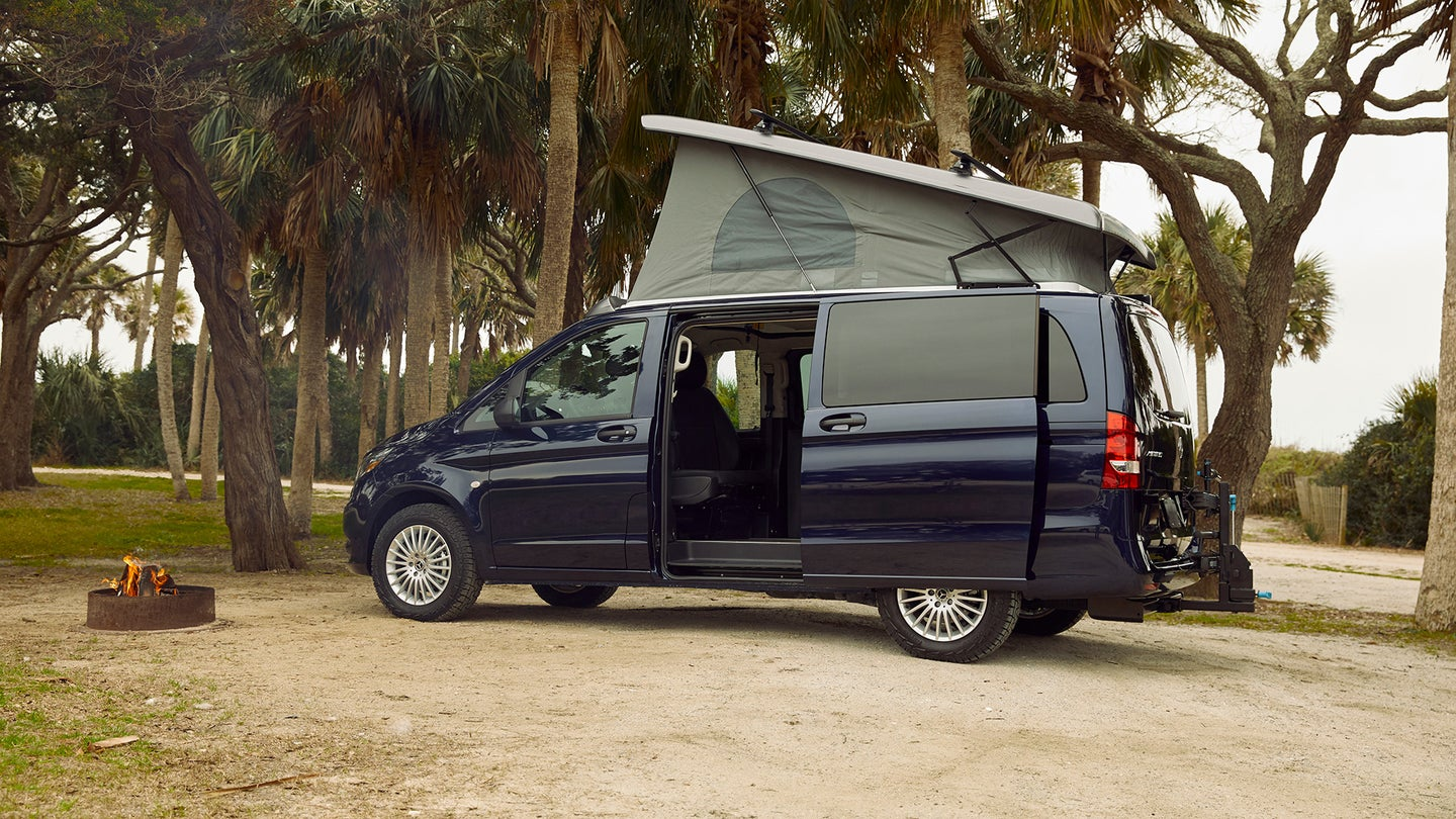 A Mercedes-Benz camper van with a pop-top next to a campfire in the woods.