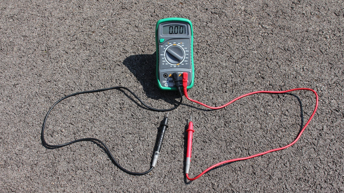 A multimeter on the ground in a parking lot.