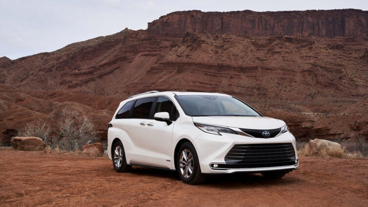 A white Toyota Sienna hybrid poses in front of a rock formation.