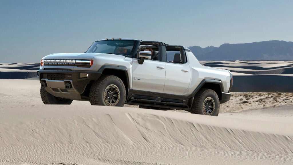 A 2022 GMC Hummer electric truck on white sand dunes.