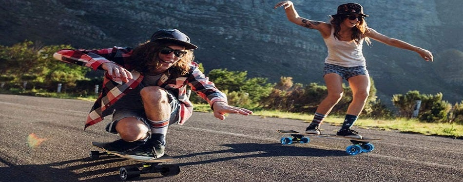 Young couple is riding cruiser skateboards in mountains