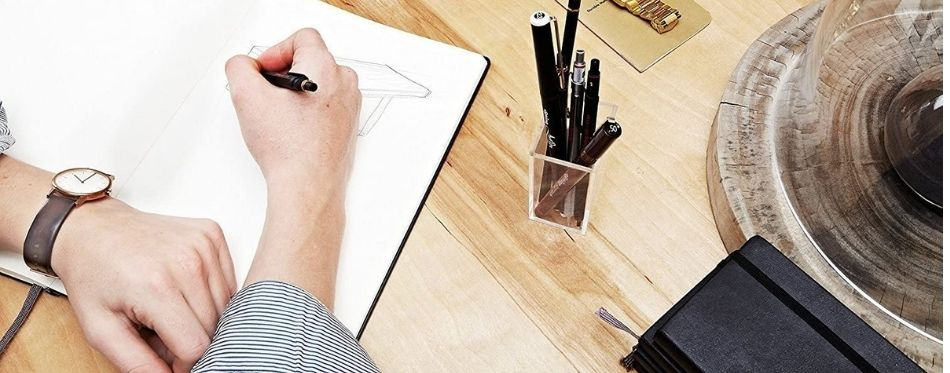 Man drawing with mechanical pencil on a table