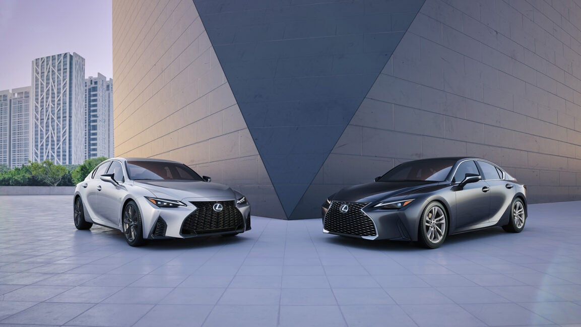 The new Lexus IS poses in front of a modern geometric building.