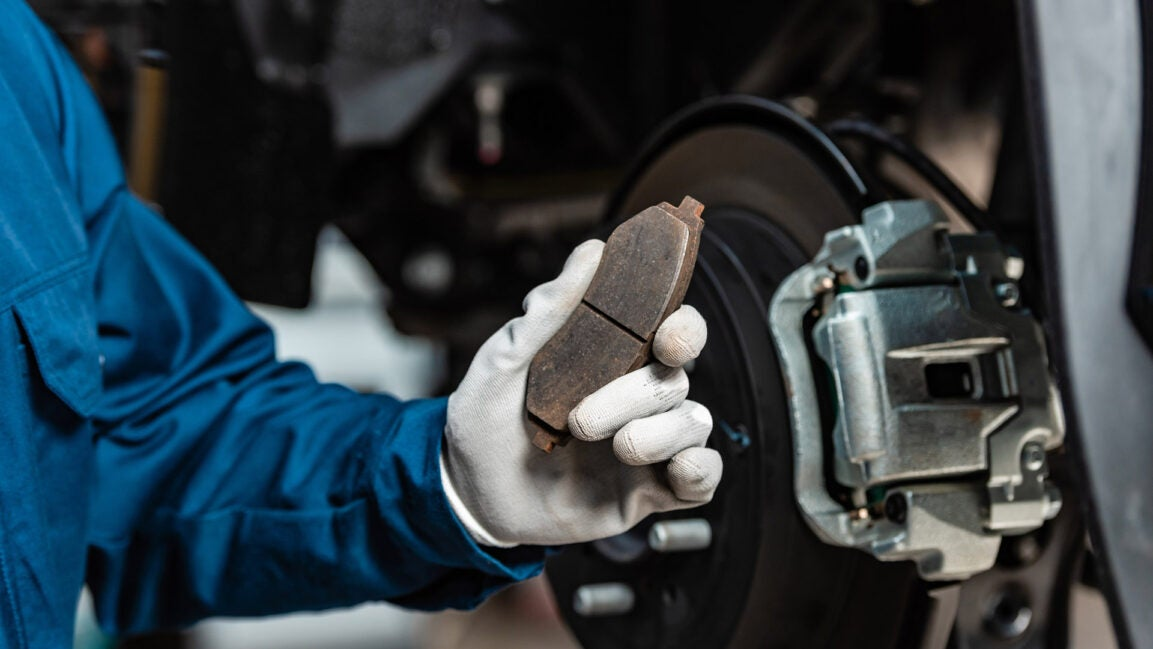 A mechanic holds up a brake pad with a glove.