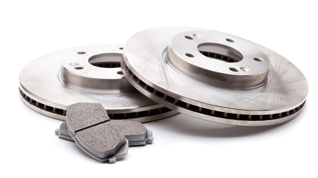 New brake rotors and pads sit on a white background.