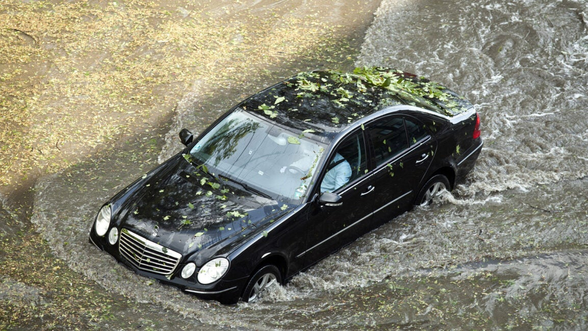 A Black Mercedes-Benz driving through water.
