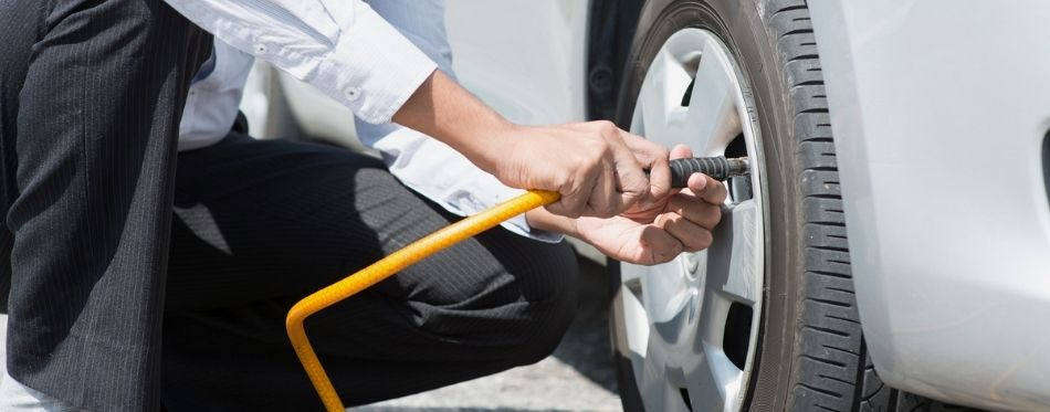 Man inflating tire with car tire inflator