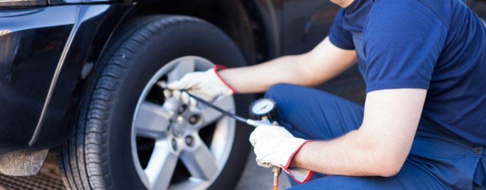 Mechanic inflating tire with car tire inflator