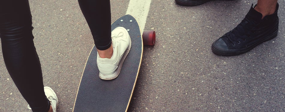 two peoples wearing longboarding shoes while skeatboarding