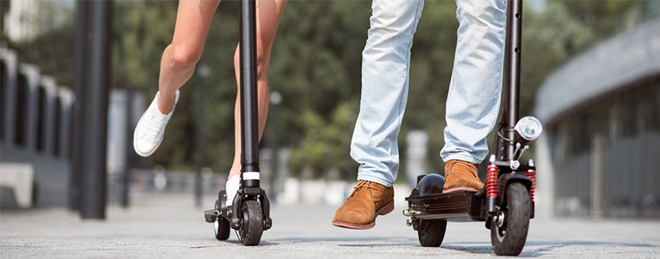 couple moving around the city with best electric scooter for commuting
