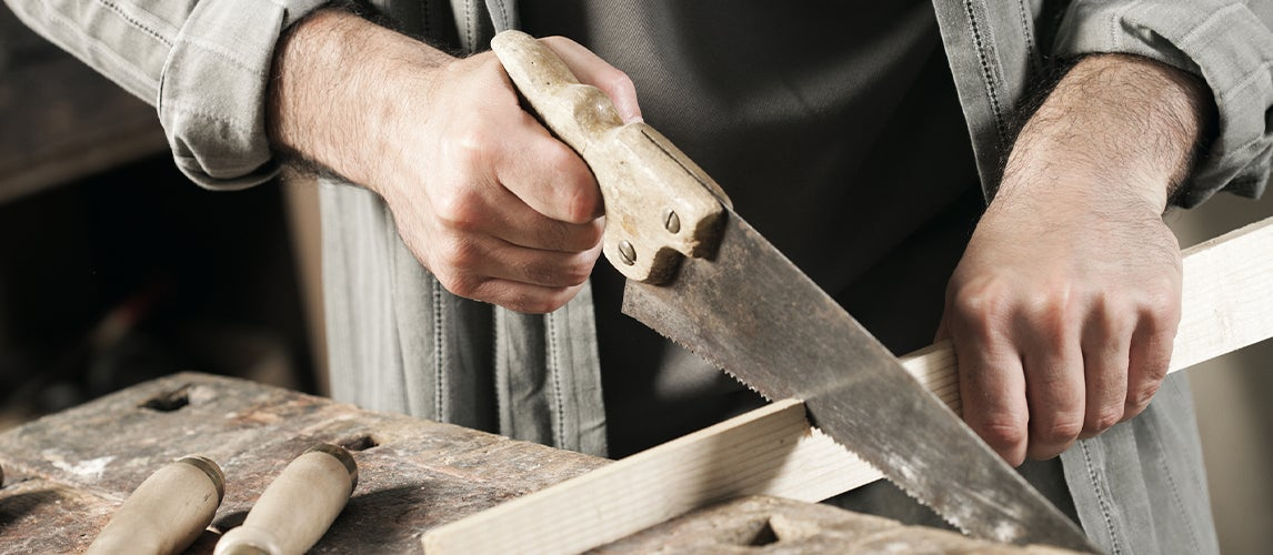 Handsome carpenter working with dovetail saws