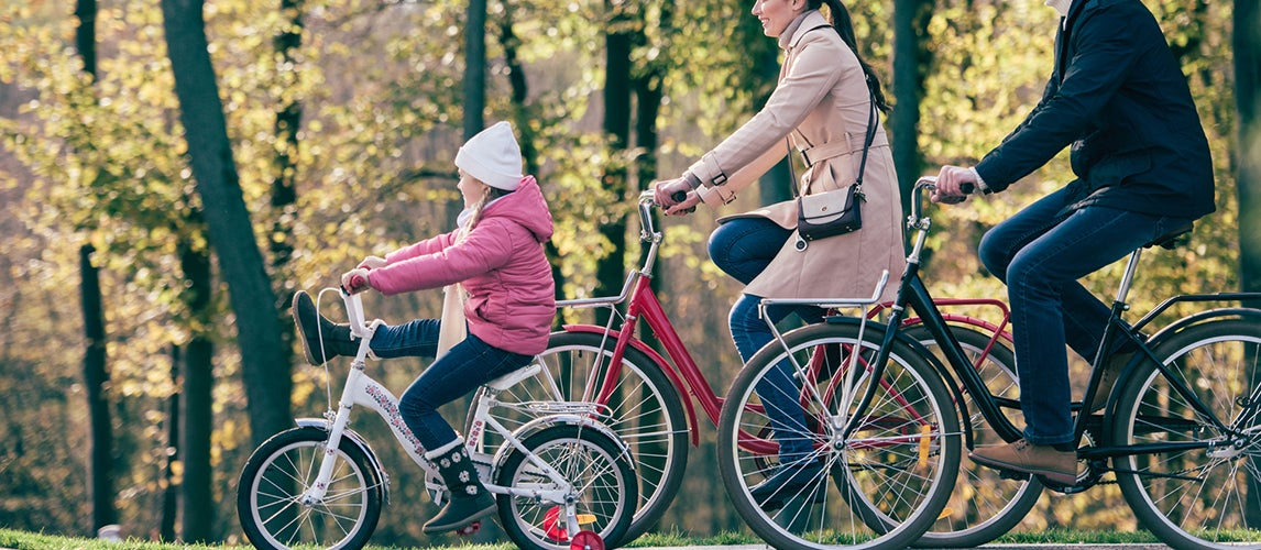 little girl taking a ride with her family with girls bike