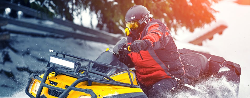 man driving a snowmobile safe with snowmobile helmet