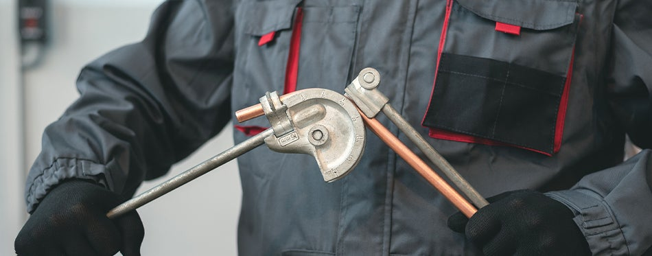 tube bender tool in hands of a worker