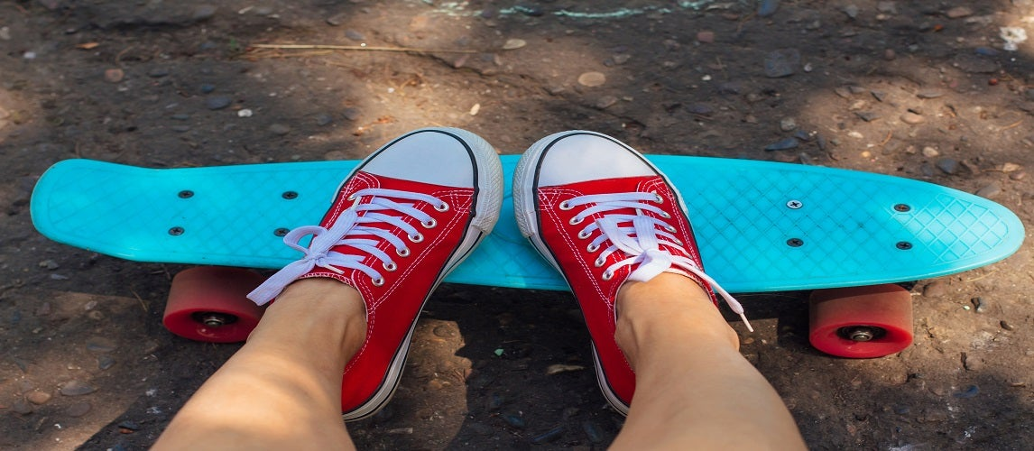 Close up of feet and blue cruiser skateboards with pink wheels.