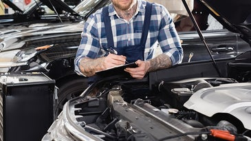 young mechanic trying to replace electric fuel pump