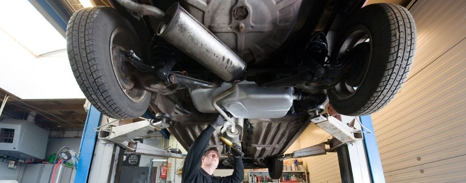 Mechanician fixing car exhaust with sealant