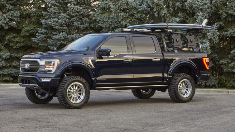 A lifted Ford F-150 carries a surfboard.