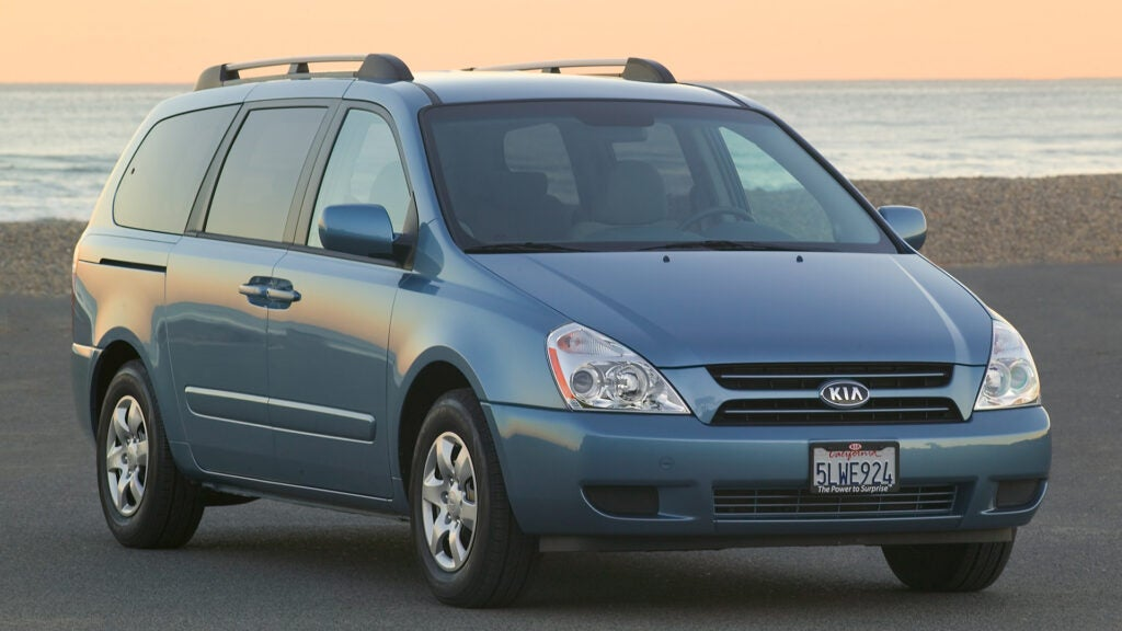 A blue Kia Sedona in front of the ocean.