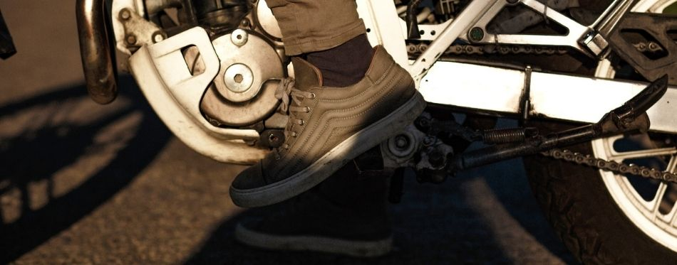 Close view of legs in motorcycle shoes on a motorbike