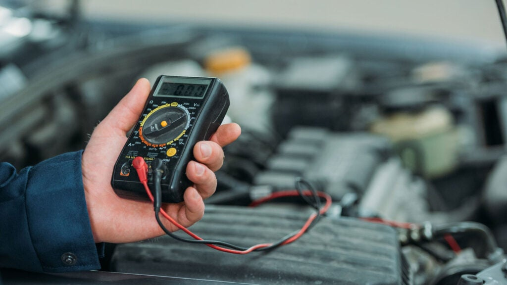 A mechanic holds a multimeter in his hand.